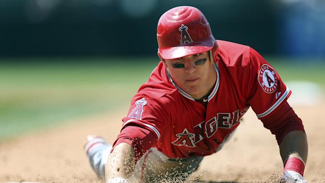 FILE - In this June 10, 2012, file photo, Los Angeles Angels' Mike Trout dives safely back to first to beat the tag by the Colorado Rockies during the fifth inning of an interleague baseball game in Denver. Trout unanimously won the American League Rookie of the Year Monday, Nov. 12. (AP Photo/Jack Dempsey, File)