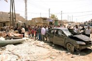 Handout photo from the Syrian Arab News Agency shows residents gathered around the reckage caused by a car bomb in the Syrian city of Aleppo on May 5. Syria&#39;s authorities and the opposition traded accusations Sunday over who was behind blasts that rocked Damascus and Aleppo, on the eve of parliamentary polls designed to boost the regime&#39;s legitimacy