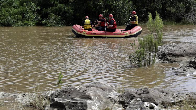 Members of a the Shertz Fire Department search Sunday, May 26, 2013, in Shertz, Texas, for a missing teen who was swept away in a rain swollen Cibilo Creek Saturday. (AP Photo/Eric Gay)