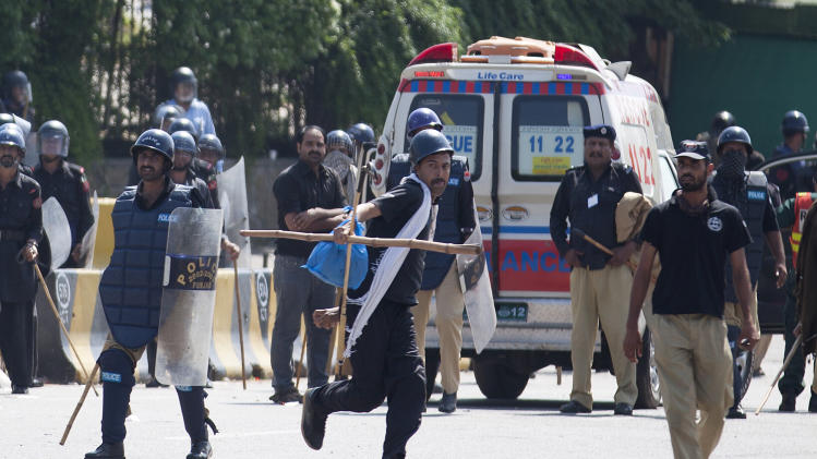 A police officer throws rocks to disperse protesters outside the parliament building in Islamabad, Pakistan, Sunday, Aug. 31, 2014. Pakistani police are clashing with scattered pockets of anti-government protesters trying to advance on the prime minister's residence after a night of violence that saw hundreds wounded and the first death Sunday in more than two weeks of demonstrations. (AP Photo/B.K. Bangash)