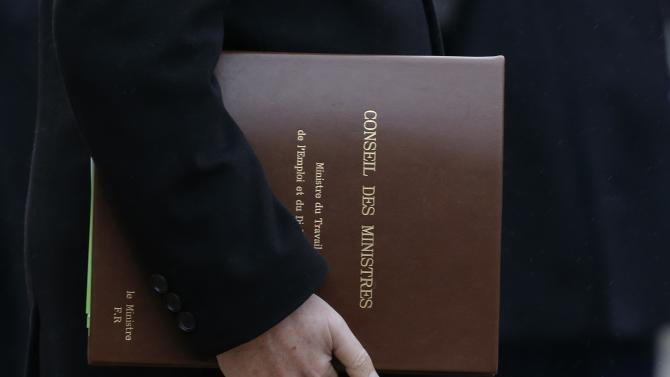 French Labour minister Rebsamen holds files as he leaves the Elysee Palace in Paris