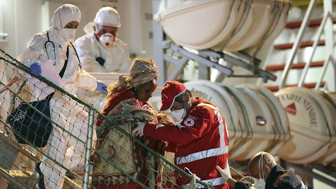 Woman is helped to disembark from tug boat Asso29 in the Sicilian harbour of Pozzallo, southern Italy