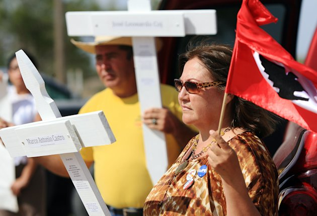 During a news conference and vigil held Thursday Nov. 1, 2012 near La Joya, Texas, Alicia Zavala holds a cross dedicated to an illegal immigrant killed who was killed when a Texas trooper who fired on a the bed of a fleeing pickup truck on Oct. 25 from a helicopter near the U.S.-Mexico border. The trooper has returned to work but in a different role, the state Department of Public Safety said Thursday. The announcement came less than an hour after the American Civil Liberties Union and local civil rights organizations gathered near the site of the Oct. 25 shooting to demand an investigation by an independent body outside the agency. (AP Photo/The Monitor, Gabe Hernandez)