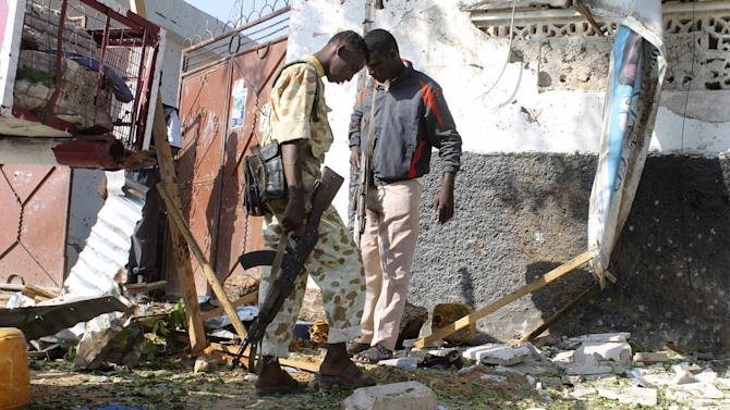 Somali soldiers search the debris after a two suicide bombers attacked a popular restaurant in Mogadishu, Somalia, Saturday Nov. 3, 2012. Three people, including two suicide bombers died in the attack. ( AP Photo/Farah Abdi Warsameh)