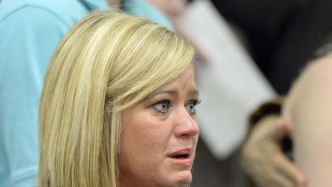 Stephanie Wardrip of Danville, Ky. fights back tears during the memorial service remembering the 25th anniversary of the Carrolton bus crash at North Hardin High School Tuesday, May 14, 2013 in Radcliff, Ky. (AP Photo/Timothy D. Easley)