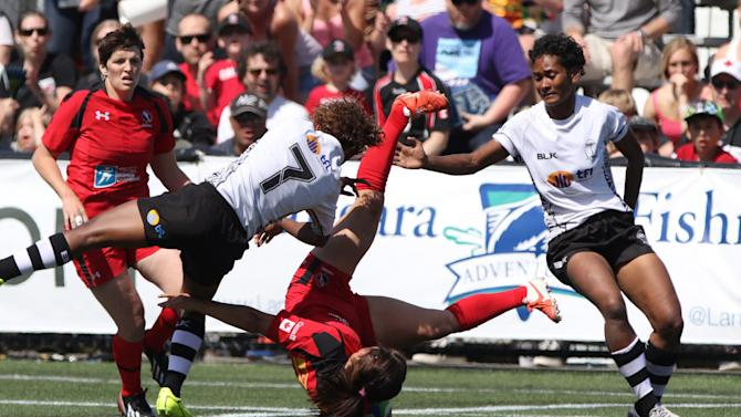 Canada's Ashley Steacy, goes flying after a hit from Fiji's Ana Roqica (left) during rugby action at the Women's Sevens at Westhills Stadium in Langford, British Columbia, Sunday April 19, 2015. Canada beat Fiji 45-0 advancing to the plate final against the U.S.   (Chad Hipolito/The Canadian Press via AP)