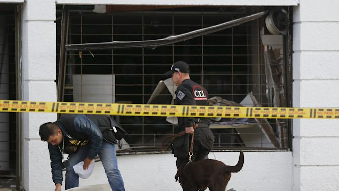 Policemen inspect the site of an explosion with a bomb sniffing dog, in front of the office of the Porvenir pension fund in downtown Bogota