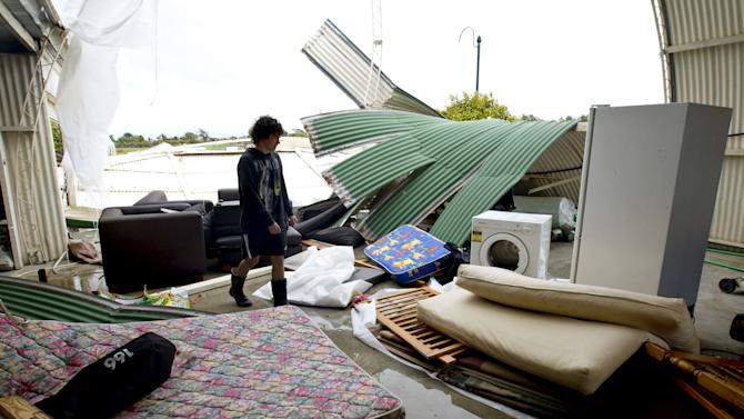 Cale Wood inspects his shed where debris was tossed around in Auckland, New Zealand, following a tornado Thursday, Dec. 6, 2012. A small tornado ripped through the city killing three people and forcing 250 more to evacuate damaged and powerless homes.  (AP Photo/New Zealand Herald, Dean Purcell) AUSTRALIA OUT, NEW ZEALAND OUT