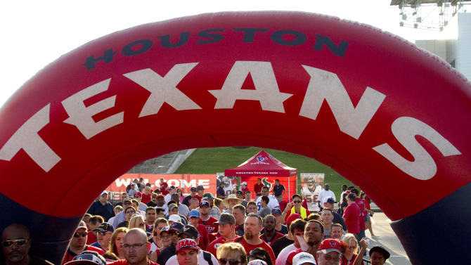 Houston Texans fans walk under an inflatable arch on their way to watch practice during an NFL football training camp Saturday, Aug. 6, 2011, in Houston.  (AP Photo/Houston Chronicle, Brett Coomer)