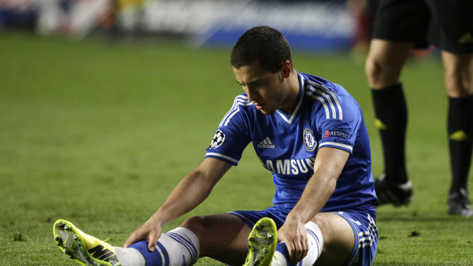 Chelsea's Eden Hazard looks at his boots as he sits on the ground following a fall during the Champions League semifinal second leg soccer match between Chelsea and Atletico Madrid at Stamford Bridge stadium in London, Wednesday, April 30, 2014. (AP Photo/Matt Dunham)