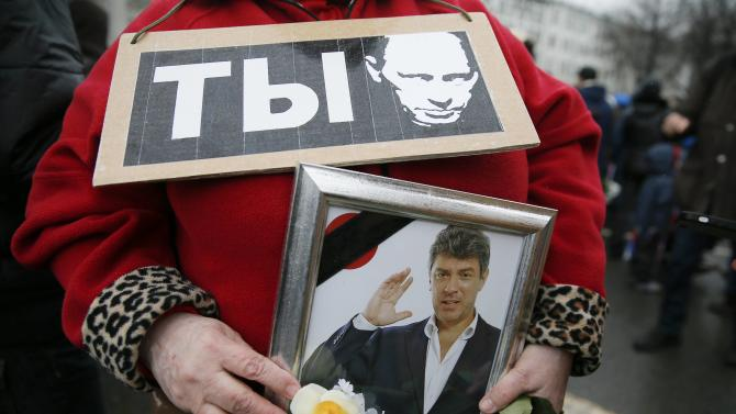 A woman holds a sign with an image depicting Russian President Putin and a photograph of Kremlin critic Nemtsov, who was shot dead on Friday night, during a march to commemorate Nemtsov in central Moscow