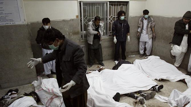 Volunteers gather next to the dead bodies of the victims of a bomb blast at the morgue of local hospital in Quetta, Pakistan on Saturday, Feb. 16, 2013. Senior police officer Wazir Khan Nasir said the bomb went off in a Shiite Muslim-dominated residential suburb of the city of Quetta. Residents rushed the victims to three different hospitals. (AP Photo/Arshad Butt)
