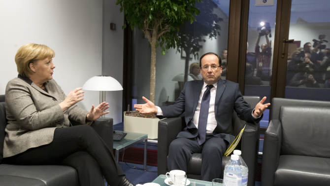 German Chancellor Angela Merkel, left, speaks with French President Francois Hollande during a meeting on the sidelines of an EU summit in Brussels on Thursday, Dec. 13, 2012. In one whirlwind morning, the European Union nations agreed on the foundation of a fully-fledged banking union and Greece's euro partners approved billions of euros in bailout loans that will prevent the nation from going bankrupt. (AP Photo/Michel Euler, Pool)