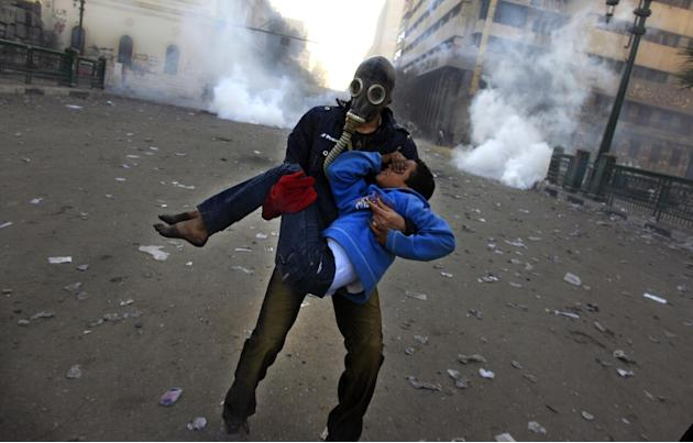 An Egyptian protester evacuates an injured boy during clashes near Tahrir Square, Cairo, Egypt, Friday, Jan. 25, 2013. Two years after Egypt's revolution began, the country's schism was on display Fri