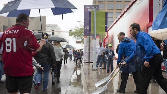 Kohl Wright right, and Mike Kilsdonk shovel water off of the sidewalk outside the Verizon Power House, Friday, Jan. 30, 2015, in Phoenix, two days before the NFL football Super Bowl in Glendale, Ariz. (AP Photo/The Arizona Republic, Mark Henle)