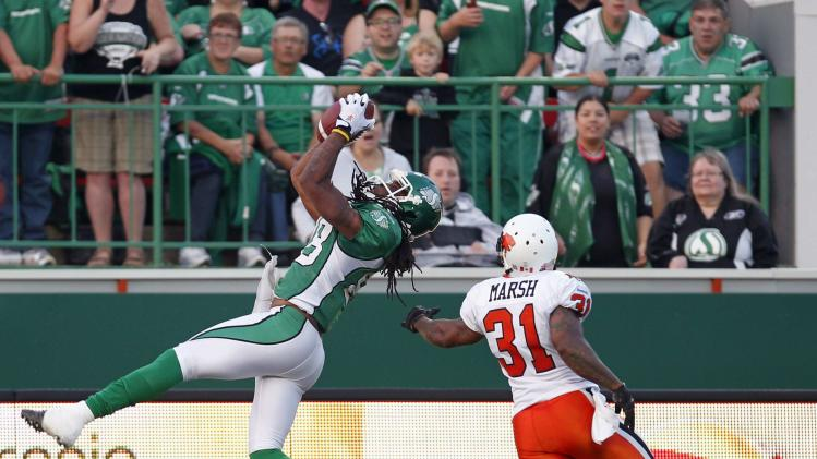 Saskatchewan Roughriders wide receiver Taj Smith catches the ball before being hassled by BC Lions corner back Dante Marsh during CFL game in Regina