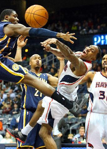 Hawks point guard Jeff Teague is forced to pass it off under the basket by Indiana Pacers center Ian Mahinmi, left, during the second half of a preseason NBA basketball game on Tuesday, Oct. 22, 2013,