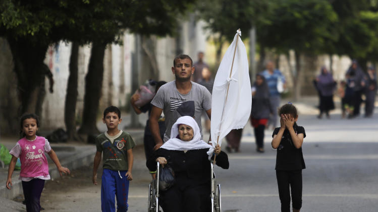 A Palestinian wheels an elderly woman holding a white flag as they flee their homes in the Shajaiyeh neighborhood of Gaza City, northern Gaza Strip, Sunday, July 20, 2014. Hundreds of panicked residents have fled the neighborhood which they say has come under heavy tank fire from Israeli forces. Some reported seeing dead and wounded in the streets, with ambulances unable to reach the area. Israel widened its ground offensive early Sunday, sending more troops into the Hamas-ruled territory to destroy tunnels used by the Islamic militants to try to sneak into Israel. (AP Photo/Hatem Moussa)