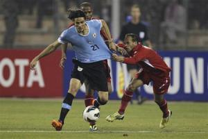 Edinson Cavani of Uruguay fights for the ball with Adnan Adous of Jordan during their World Cup qualifying playoff first leg soccer match at Amman International stadium