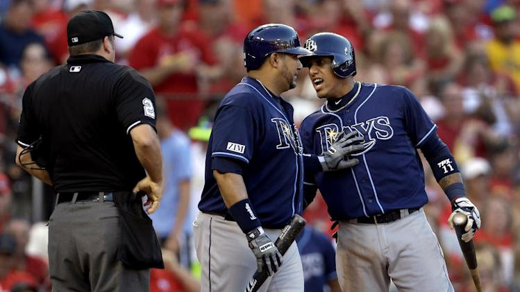 Tampa Bay Rays' Yunel Escobar, right, is held back by teammate Jose Molina after being ejected by home plate umpire Dan Bellino, left, during the fourth inning of a baseball game against the St. Louis Cardinals, Wednesday, July 23, 2014, in St. Louis. (AP Photo/Jeff Roberson)