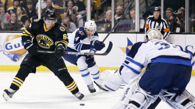 Boston Bruins' Brad Marchand (63) tries to get off a shot on Winnipeg Jets goalie Ondrej Pavelec (31), of the Czech Republic, as Paul Postma (4) defends during the second period of an NHL hockey game in Boston, Monday, Jan. 21, 2013. (AP Photo/Michael Dwyer)