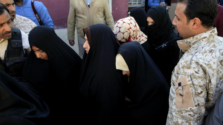 An Iraqi policeman stands near female detainees to be released in the Iraqi Interior Ministry in Baghdad, Iraq, Monday, Jan. 14, 2013. Protesters in predominantly Sunni parts of Iraq have been demonstrating for more than three weeks against what they see as unfair treatment by the government against their sect. The release of detainees held without charges has been one of their main demands. (AP Photo/Karim Kadim)