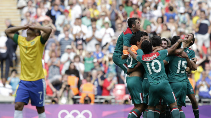 Brazil's Lucas reacts as Mexico's players celebrate their victory over Brazil after their men's soccer final gold medal match at Wembley Stadium during the London 2012 Olympic Games