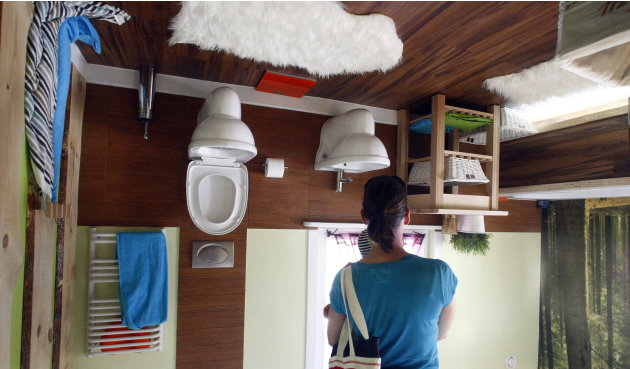 Woman stands inside bathroom of house, which was built upside down by Polish architects Glowacki and Rozhanski, in western Austrian village of Terfens