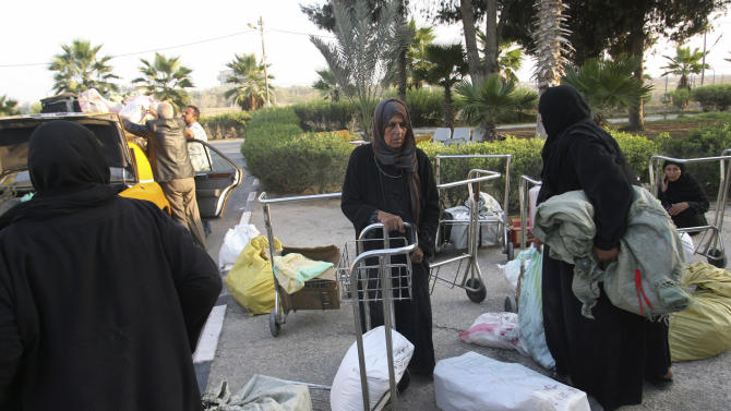 Palestinian women arrive in Rafah after crossing into Gaza Strip from Egypt, Tuesday, Nov. 20, 2012. The $1.4 million terminal reflects a sign of Palestinian hopes that the fighting over the past week will end with a deal leading to an easier flow of people and goods into Egypt, which would transform their lives in the impoverished territory. It would also give Hamas a major victory that could help the Islamic group tighten its grip over Gaza's 1.7 million residents. (AP Photo/Eyad Baba)