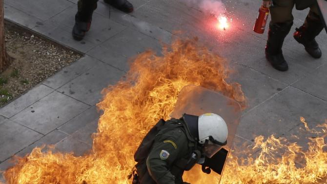 Riot police officers back away from a petrol bomb thrown by protesters during a 24-hour nationwide general strike in Athens, Thursday, Feb. 4, 2016. Clashes have broken out between Greek police and youths throwing fire bombs and stones, as tens of thousands of people march through central Athens to protest planned pension reforms. (AP Photo/Thanassis Stavrakis)