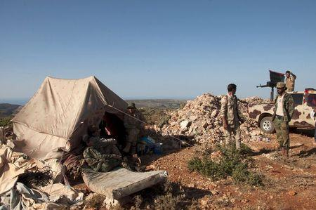 Members of the Libyan pro-government forces, stand near their tent during their deployment in the Lamluda area, southwest of the city of Derna