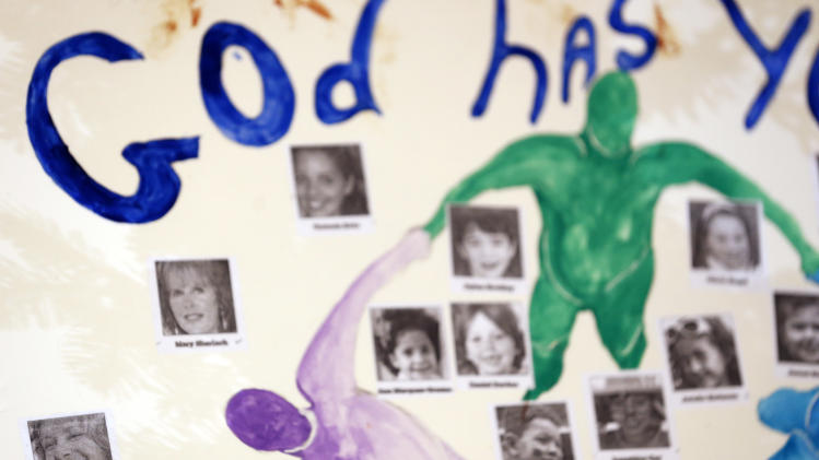 A photograph of Nancy Lanza, bottom left, one of the 27 people allegedly killed by Adam Lanza in the Sandy Hook village of Newtown, Conn., last week, appears on a board at a makeshift memorial, Thursday, Dec. 20, 2012. For the most part, makeshift memorials honor the 26 victims allegedly killed by the gunman, who forced himself into Sandy Hook Elementary School on Dec. 14, 2012. In total, 27 people were killed as officials say Lanza shot and killed his mother, Nancy Lanza, at their home. Nancy Lanza is virtually nonexistent in the memorials. (AP Photo/Julio Cortez)