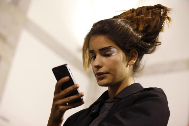 A model looks at her mobile phone backstage before a presentation by fashion designer Lidija Kolovrat for the Fall/Winter 2014/15 collection during Lisbon Fashion Week