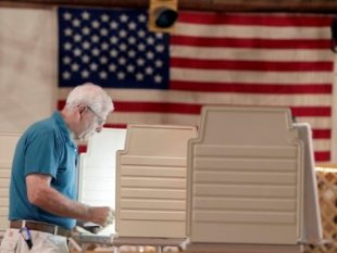 A man votes at a polling station.