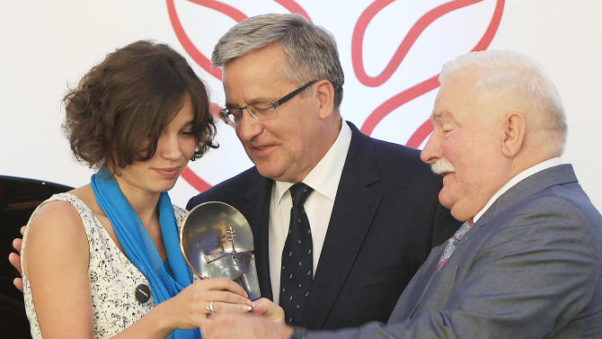 Zhanna Nemtsova, left, the daughter of slain Russian opposition leader Boris Nemtsov  stands  next to Poland's President Bronislaw Komorowski  center, and former president. Lech Walesa, right, after receiving Poland's 4 million zlotys ( US $1 million, 964,000 euros) Solidarity award in recognition of her father's and her own activity at the Presidential Palace in Warsaw, Poland, on Tuesday, Aug. 4, 2015.(AP Photo/Czarek Sokolowski)