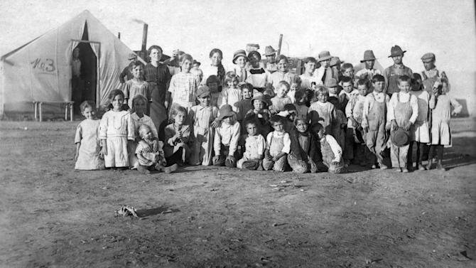 This 1914 photo provided by the Denver Public Library, Western History Collection, shows children and some adults posing for a photo at camp Ludlow in south central Colorado. Two women and 11 children died in a fire at the camp during a battle between the Colorado National Guard and striking coal miners. Sunday April 20, 2014 is the 100th anniversary of the Ludlow Massacre. (AP Photo/Denver Public Library, Western History Collection)