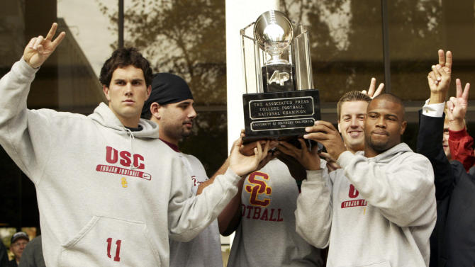 FILE - In this Jan. 5, 2004 file photo, Southern California players Matt Leinart, left, Shaun Cody, second from right, and Marcell Allmond, right, celebrate after being awarded the Associated Press' national college football trophy during ceremonies on the steps of Heritage Hall on the Los Angeles campus. It is the school's first national title in 25 years, but one they share with Bowl Championship Series winner LSU. (AP Photo/Ric Francis, File)