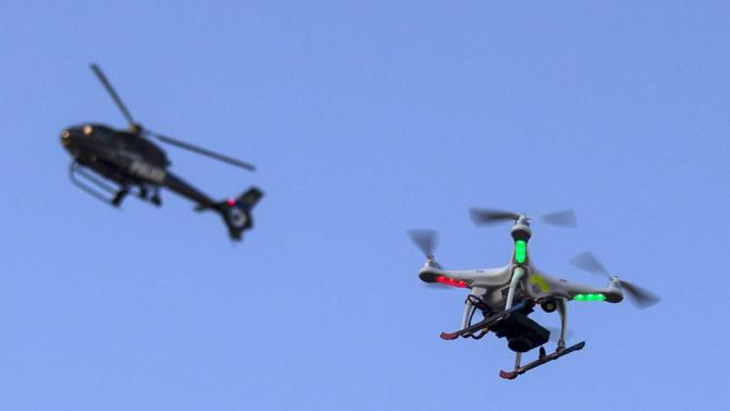 A police helicopter flies past a UAV drone which was flying over a post-march street celebration in west Baltimore, Maryland
