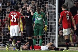 Referee Michael Oliver signals on the medics as Manchester United's Vidic lays injured during their English Premier League soccer match against Arsenal in Manchester