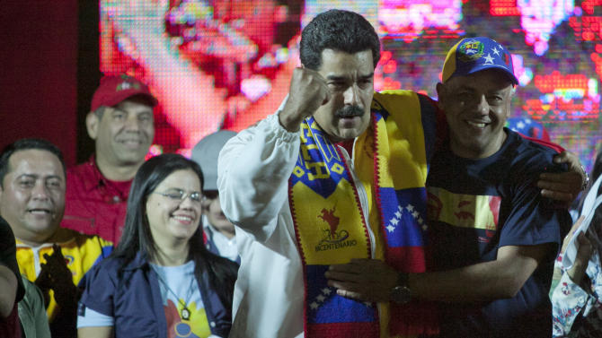 Venezuela's President Nicolas Maduro, left, celebrates with Jorge Rodriguez who was reelected as mayor of the Libertador municipality in Caracas, Venezuela, Sunday, Dec. 8, 2013. Pro-government candidates and opponents of President Nicolas Maduro split Venezuela's disputed mayoral elections Sunday, prolonging a political stalemate in the face of mounting economic problems. (AP Photo/Alejandro Cegarra)