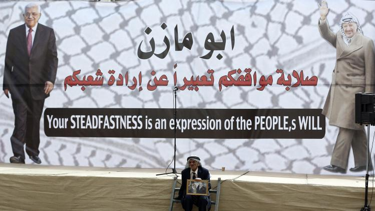 A Palestinian sits in front of a poster depicting Abbas and Arafat during a rally in Ramallah