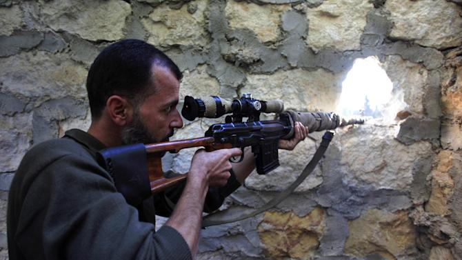 A rebel sniper aims at a Syrian army position on the outskirts of Aleppo, Syria, Wednesday, Nov. 14, 2012. Heavy clashes between rebel units and Bashar Assad's troops were ongoing in the northern city of Aleppo, the Syrian Observatory for Human Rights said Wednesday. (AP Photo/Khalil Hamra)