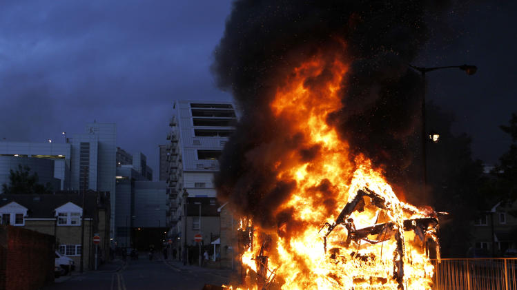 A bus is set on fire as rioters gathered in Croydon, south London, Monday, Aug. 8, 2011. Violence and looting spread across some of London's most impoverished neighborhoods on Monday, with youths setting fire to shops and vehicles, during a third day of rioting in the city that will host next summer's Olympic Games. (AP Photo/Sang Tan)