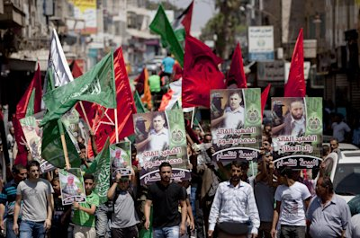 CLICK IMAGE for slideshow: Supporters of Hamas hold posters of three senior commanders of the Hamas military wing, Mohammed Abu Shamaleh, Raed Attar and Mohammed Barhoum, who were killed in Thursday's Israeli strikes, during a demonstration to protest against Israel and to support people in Gaza, in the West Bank city of Ramallah on Friday, Aug. 22, 2014. (AP Photo/Majdi Mohammed)