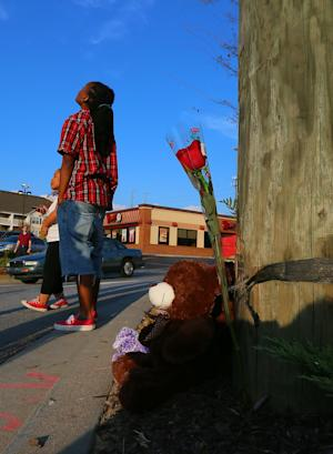 Local resident Ciara Edmonds glances up at telephone wires and lines after placing the rose at right on a shrine of the crash site where a police helicopter crashed killing two officers in Atlanta on Sunday, Nov. 4, 2012. The crash occurred Saturday during a search for a missing child. (AP Photo/Atlanta Journal-Constitution, Curtis Compton) MARIETTA DAILY OUT; GWINNETT DAILY POST OUT; LOCAL TV OUT; WXIA-TV OUT; WGCL-TV OUT.