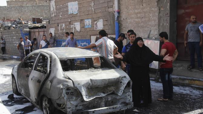 A woman reacts at the site of a car bomb attack in Kirkuk