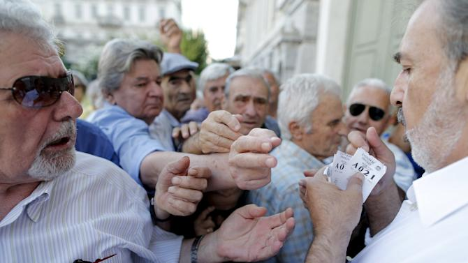 Pensioners are given priority tickets as they wait to receive part of their pensions at a National Bank branch in Athens