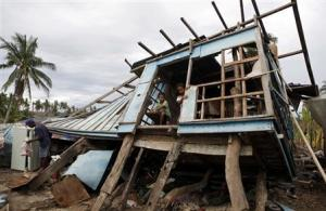 Typhoon victims look out from their house that was…