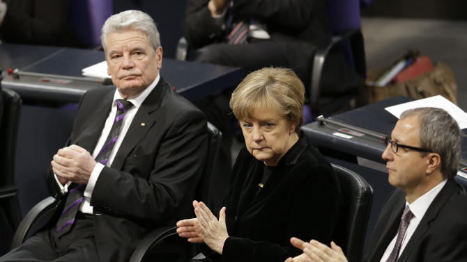 German President Joachim Gauck, German Chancellor Angela Merkel and Andreas Vosskuhle, president of the German constitutional court, from left, applaud during a ceremony commemorating the 70th anniversary of the liberation of the Nazi Auschwitz death camp in the German parliament Bundestag in Berlin, Germany, Tuesday, Jan.  27, 2015. (AP Photo/Michael Sohn)