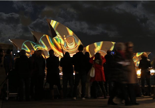 "People look at the Sydney Opera House as ""Play"" by The Spinifex Group is projected on its sails as part of Vivid Festival in Sydney"